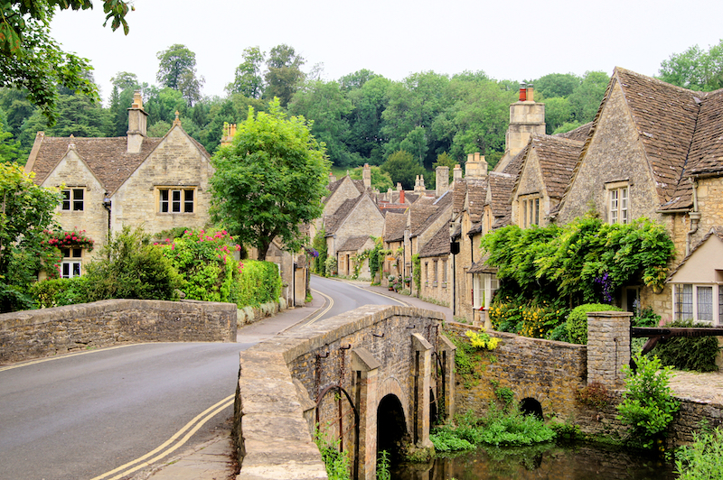 A beautiful Cotswolds village is shown, with traditional cottages shown over a bridge surrounded by trees.