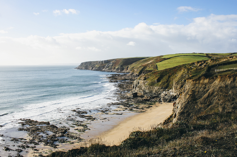 Coastline west of Porthleven on the south coast of Cornwall. Grassy cliff tops lead down to a rocky shoreline and beach. It is a sunny day and Penzance is a few miles beyond the headland.