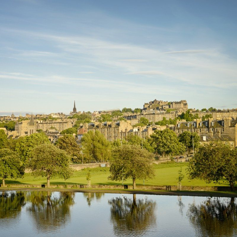 Evening view over Edinburgh from Inverleith Park, with Stockbridge and the New Town in front of the Old Town skyline, including Edinburgh Castle.