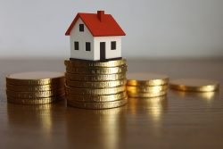 house sits on coins showing saving money using a property buying agent saving you money
