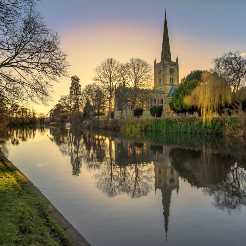 A church sits on a river, in Stratford Upon Avon at dusk.