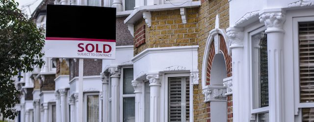 A row of terraced houses in the UK with bay windows are shown with a 'Sold' sign outside them.