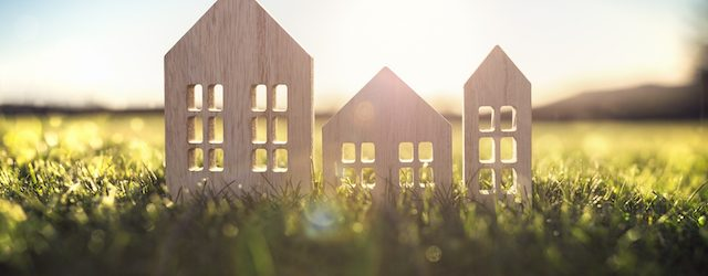 A wooden cut-out of a house sits in a green field, and sun is shining through the cut-outs for windows and doors.