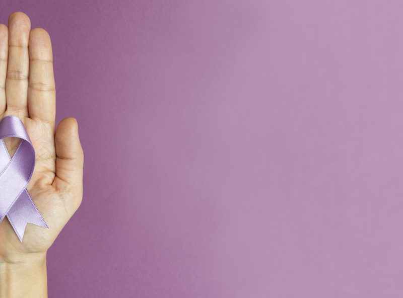 A hand holds a lilac silk ribbon in a loop against a purple background, representing Alzheimer's Awareness logo.