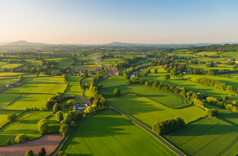 Aerial photograph of green farms and rural dwellings in the Cotswolds.