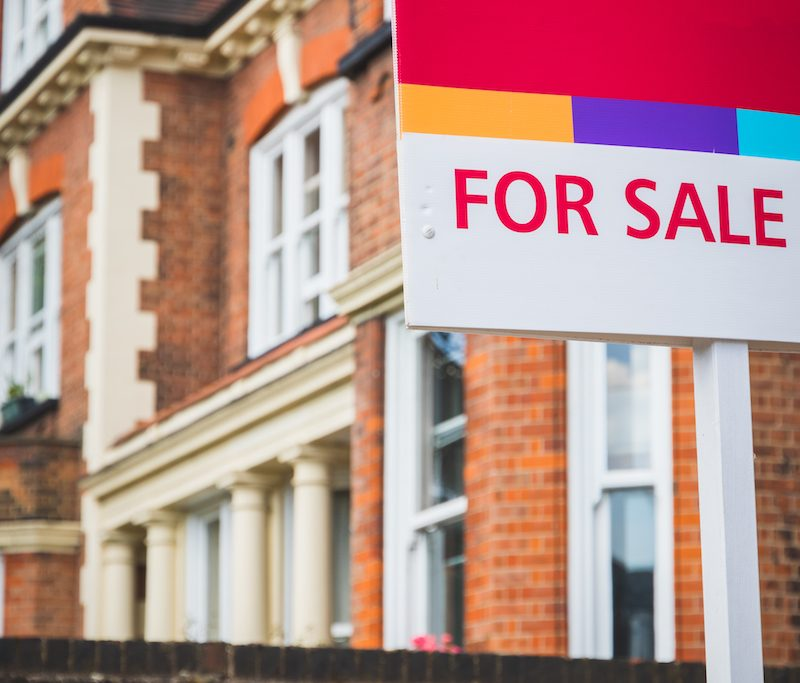 or Sale estate agent sign displayed outside a terraced house in the UK.