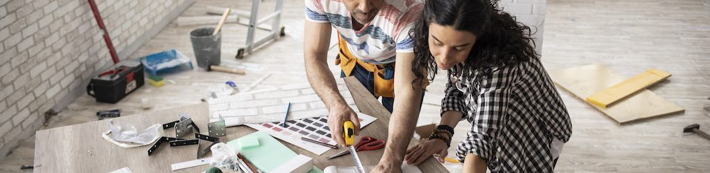 Couple making home improvement and measuring.