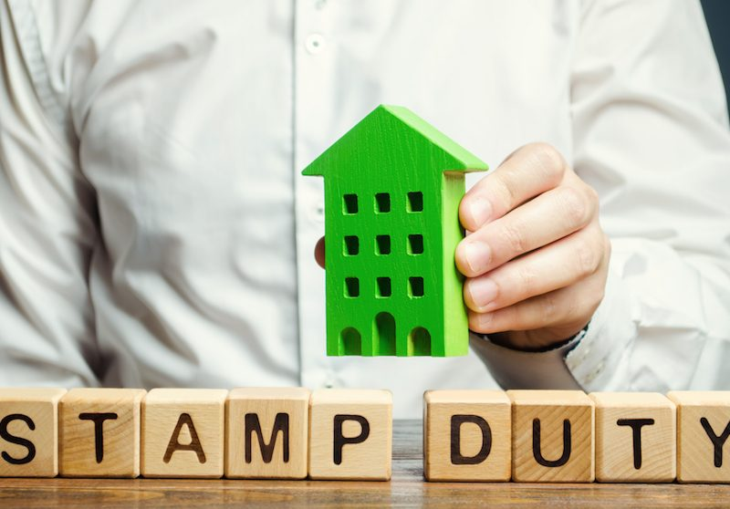 Businessman and wooden blocks with the words Stamp Duty on them.